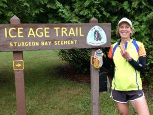 Hiker near Ice Age Trail sign for Sturgeon Bay segment.