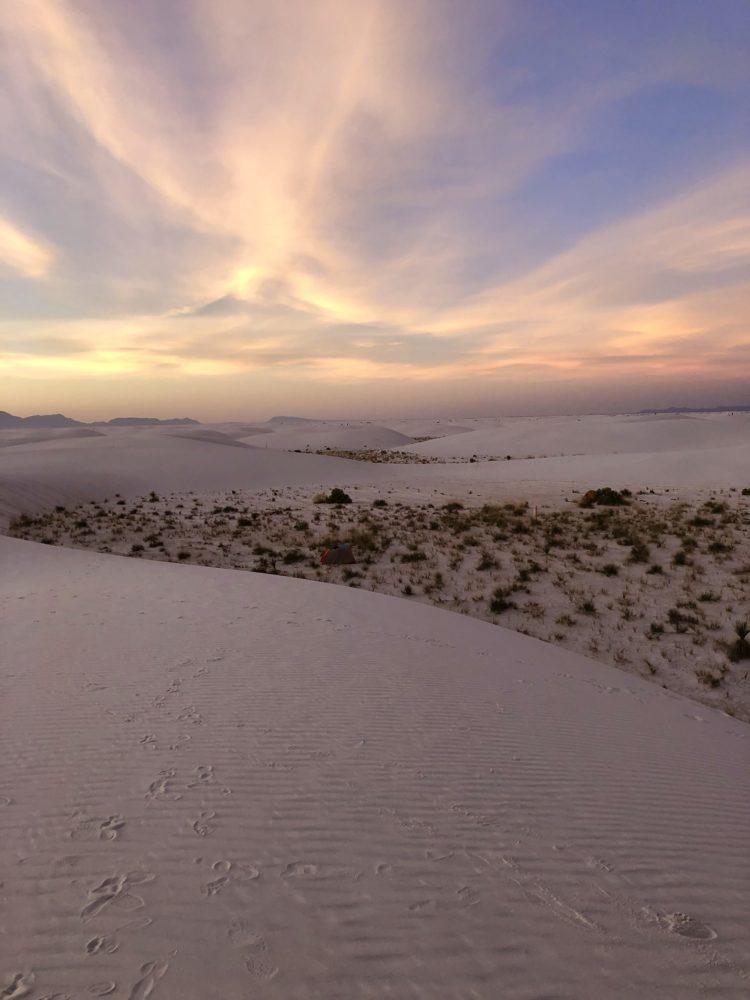 Sun setting over white sand dunes.