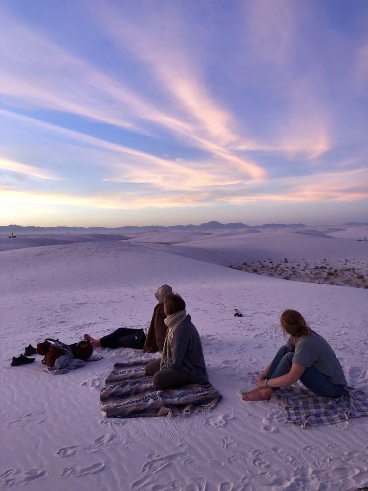 Three people sitting on white sand dunes turning purple with sunset.