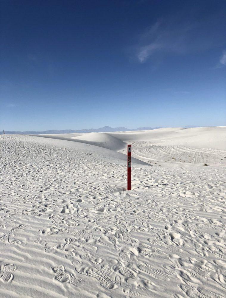 Vista of white gypsum sand dunes with an orange post marker.