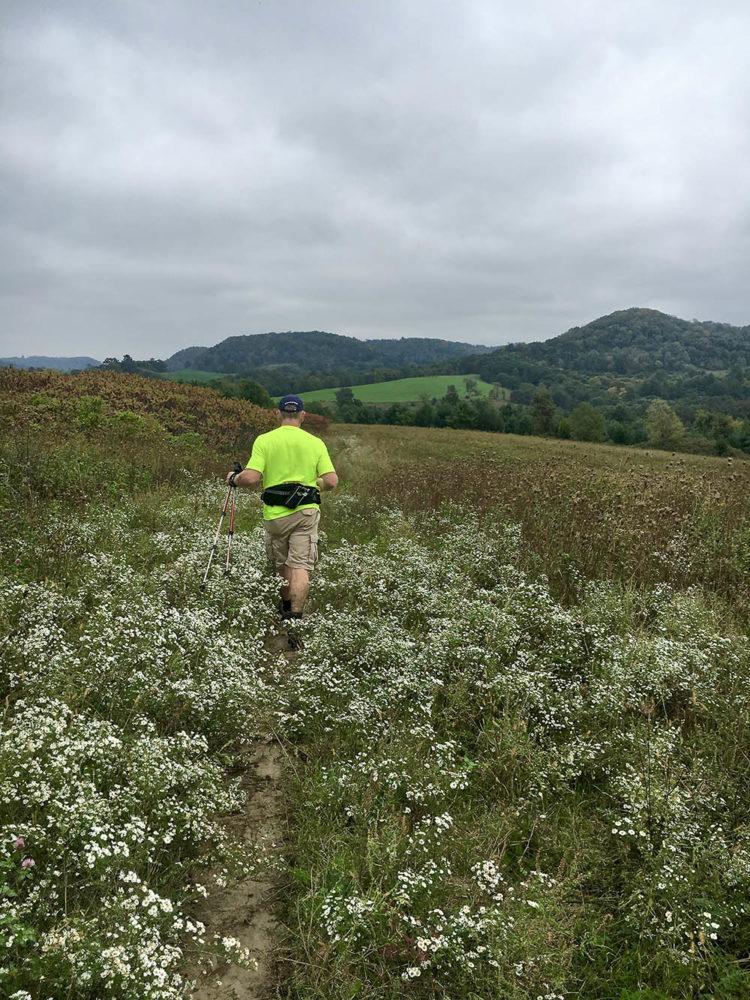 Man hiking through open field near Kickapoo Valley Ranch.