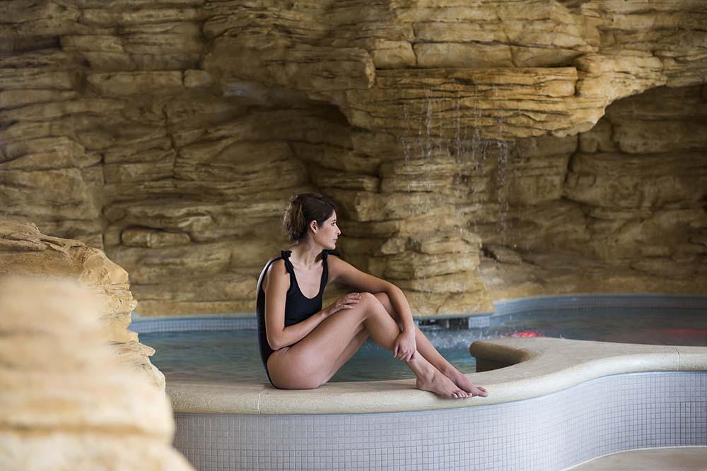 Woman relaxing by a pool at Sundara Inn & Spa.