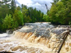 The wide Tahquahmenon Falls waterfall rushing over rocks.