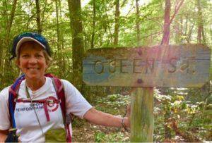 Woman hiker in forest by sign near Quabbin Reservoir