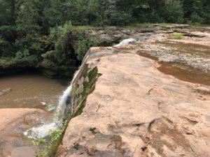 Waterfall over large, brown rock slab.