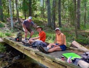 Three hikers sitting on a bridge near Spring Lake Campground.