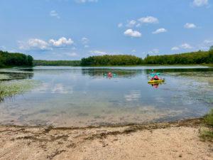 Three colorful kayaks in Nichols Lake.