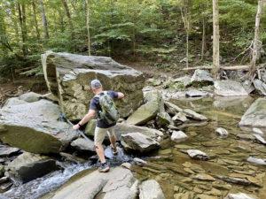 Man hopping across rocks to get across a river.