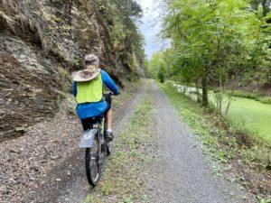 Man biking in between canal and rock wall.