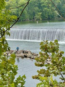 Man fishing on rocky shoal near dam.