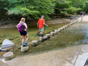 Two people walking across concrete pilings in a shallow creek.